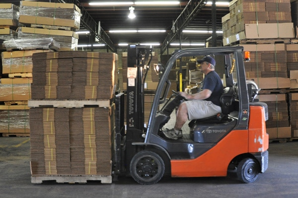 Warehouse Worker Driving Forklift with Corrugated Cardboard Boxes - Leaman Container